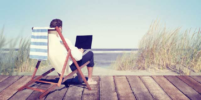 guy working remotely at the beach